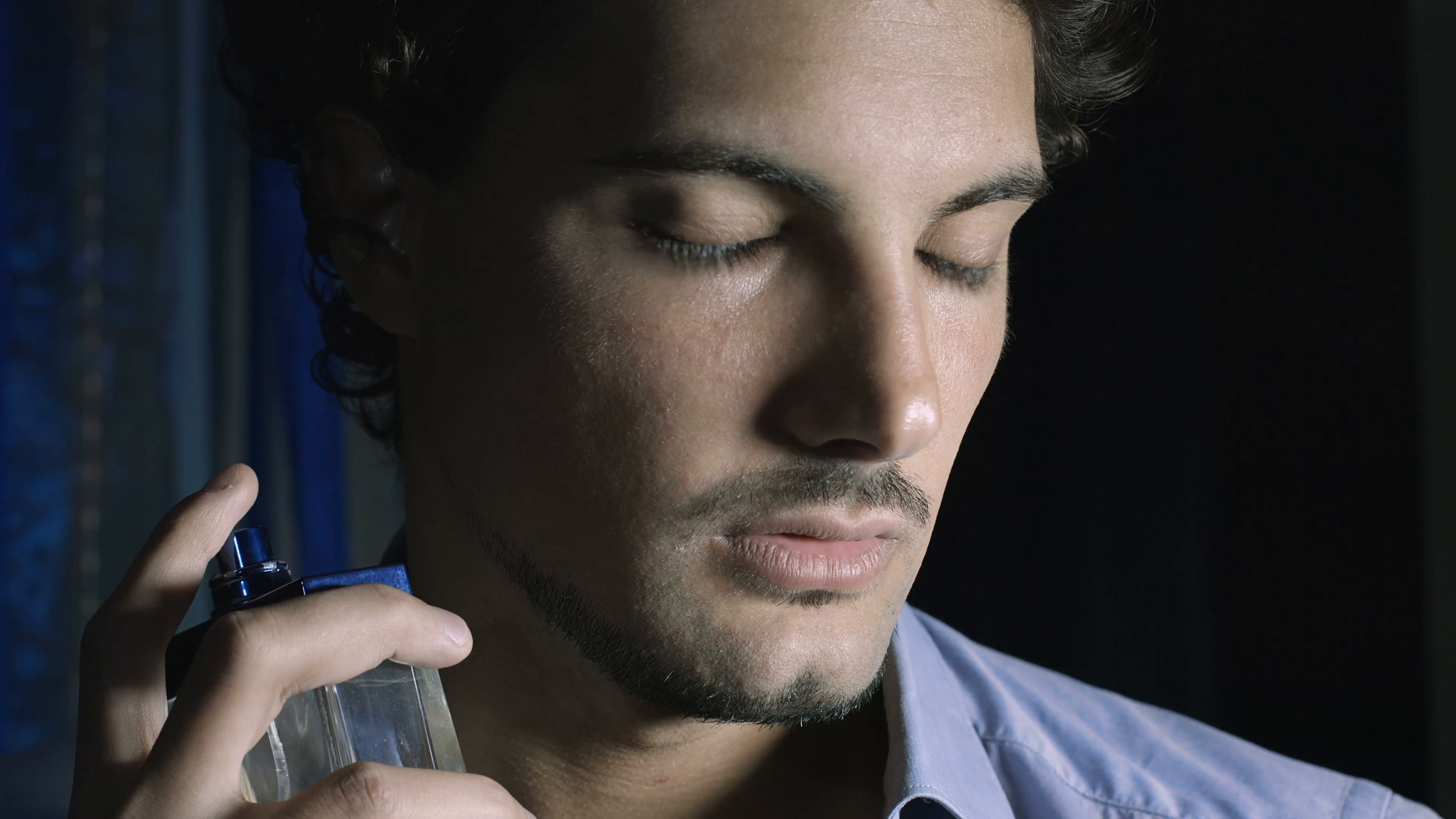 gorgeous young man spraying perfume to itself 4zmsiqcfue  F0000 - فواید استفاده از عطر برای مردان؛ شخصیت شما چه بویی میدهد؟