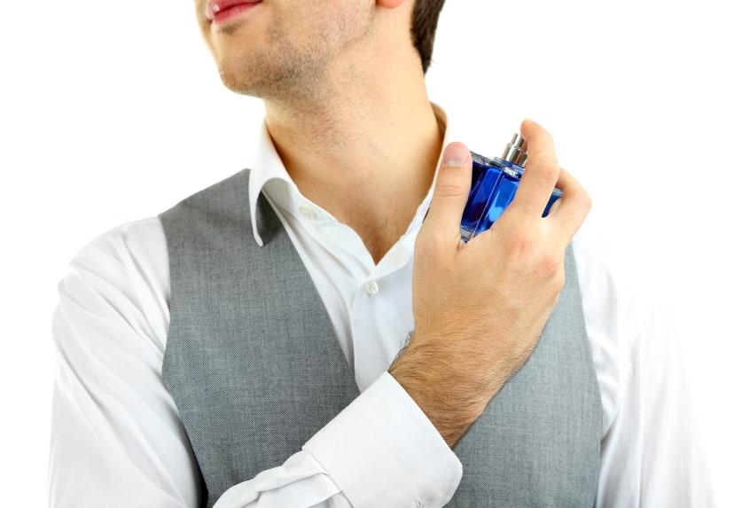 Handsome young man using perfume isolated on white - استفاده از ادکلن روی پوست  و همه آنچه که باید در مورد عوارض آن بدانید